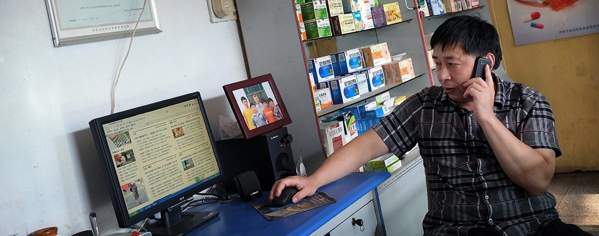 Pharmacist in rural China using smartphone and computer Gillian Bolsover